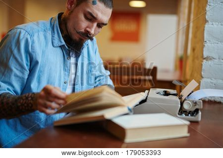Portrait of stylish creative man with tattoos and beard turning pages of old book, while using old-school typewriter in quiet inspiring atmosphere