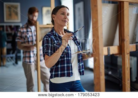 Elderly woman looking at painting on easel while working in studio of art