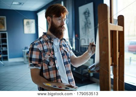 Young man with paintbrush and palette standing in front of easel in art-studio
