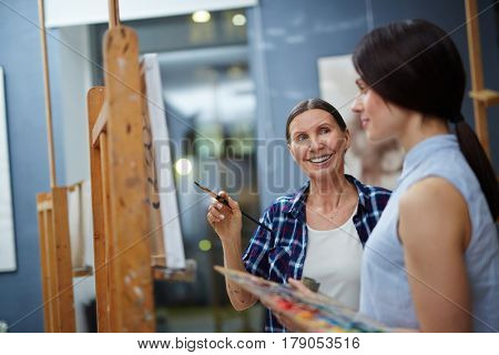 Happy teacher of arts talking to young student about her painting on canvas