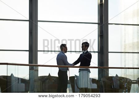 Two contemporary traders congratulating one another on successful deal