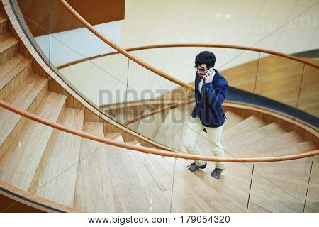 Calling businessman moving upstairs inside business center