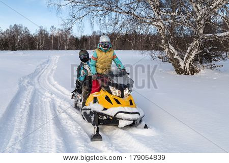 Man and woman traveling by snowmobile in the mountains of the Southern Urals.