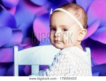 happy one year old baby in a studio against colorful background