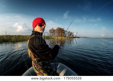 Man fishing from the boat on the lake