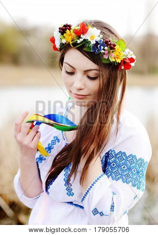 beautiful girl in a white chemise and a wreath of flowers on his head on the background of nature. Ukraine, embroidery, Ivan Kupala day, Midsummer