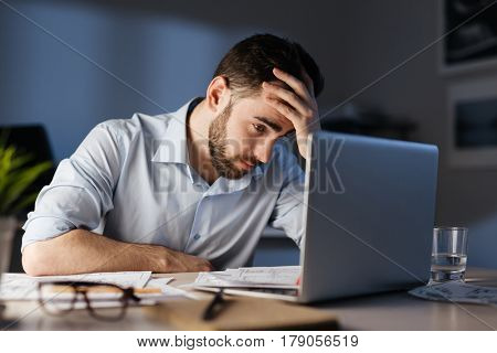 Portrait of tired bearded man working overtime alone in dark office late at night, using laptop and resting head on hand looking at screen