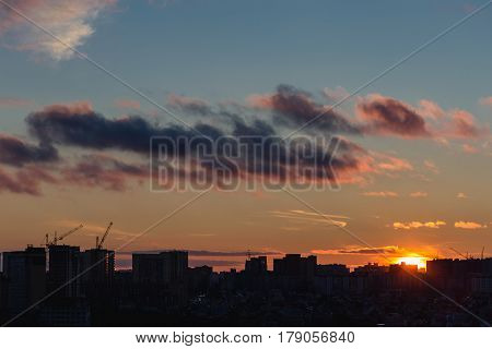Dramatic city in sunset, silhouettes of houses in the evening haze and the rays of the setting sun and clouds, evening cityscape