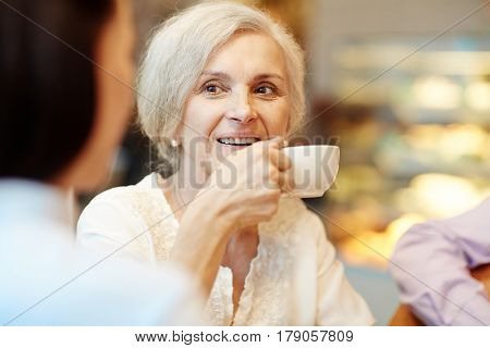 Mature woman drinking tea from white porcelain cup while talking to companion