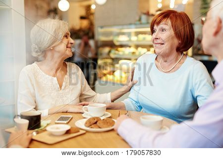 Group of mature buddies enjoying time in cafe