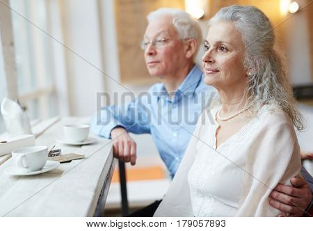 Mature man embracing his spouse while looking through window in cafe