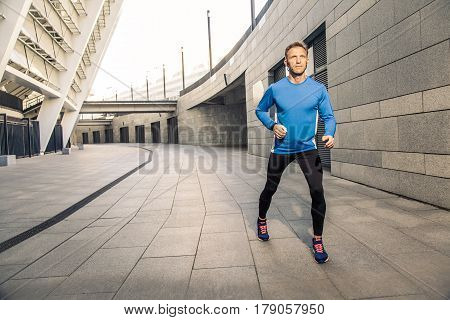 Handsome middle aged serious man in blue black sports uniform and headphones and fitness tracker is running in the city.