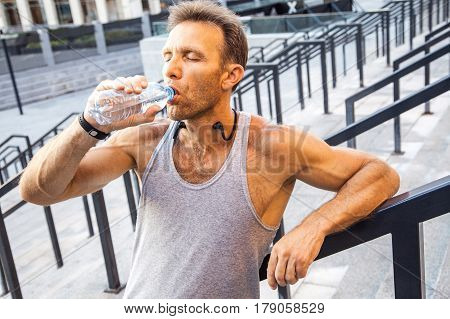 Thirsty sportsman take a rest and drinking water after running. fitness, sport, exercising and people healthy lifestyle concept.