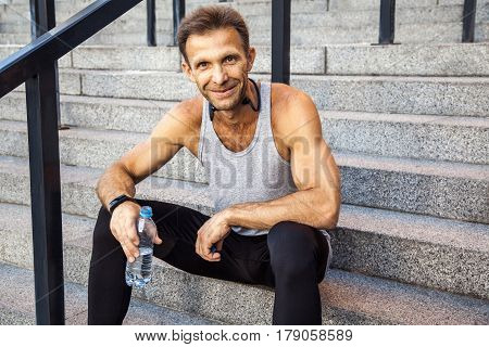 Happy smily sportsman resting and holding bottle of water, sitting on steps looking at camera and smiling . fitness, sport, exercising and people healthy lifestyle concept.