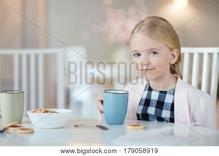 Pretty youngster drinking tea with biscuits and looking at camera