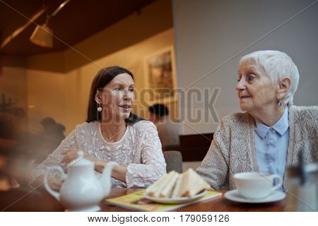 Senior buddies gathering in cafe to have cup of coffee or tea