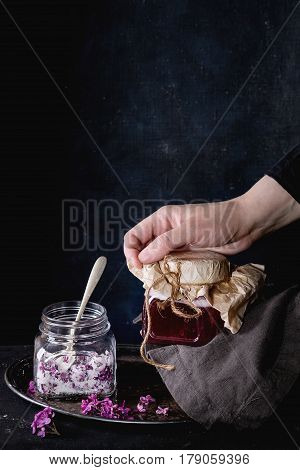 Femail hands hold glass jar of homemade lilac syrup. Glass jar of sugared lilac flowers and glass pitcher of lilac lemonade water on black tablecloth over black. Dark rustic atmosphere.