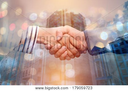 Double exposure of hands shaking a collaboration concept of teamwork and bokeh background