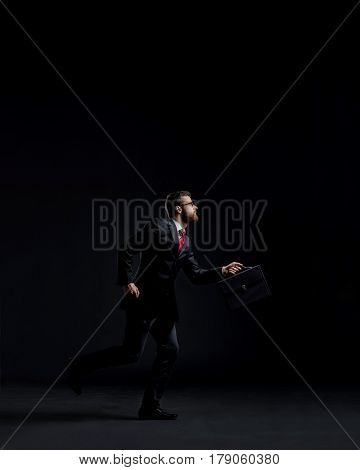 Businessman running hurry. Black background with copyspace. Time, business and office concept.