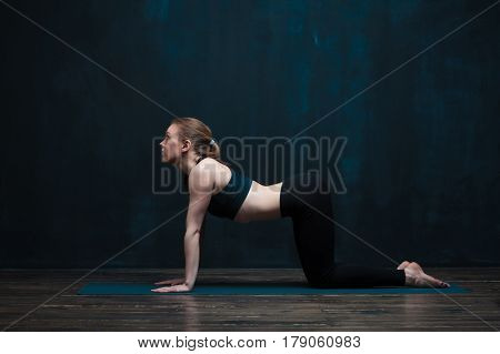 Young flexible woman wearing black sportswear practicing yoga indoors. Fit girl doing body balance exercise on blue mat. Fitness and healthy lifestyle concept.