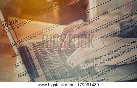 Double Exposure hand typing laptop with US tax form / taxation concept