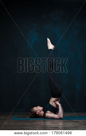 Young flexible woman working out against dark blue wall. Yoga girl practicing advanced asana indoors. Fitness and healthy lifestyle concept.