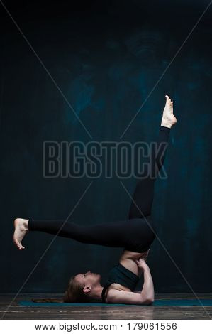 Flexible young woman practicing advanced yoga on blue mat against dark wall. Fit girl working out in class. Fitness and healthy lifestyle concept.