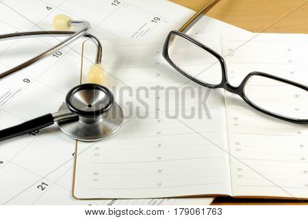 A desk top with stethoscope, address book, glasses and calendar