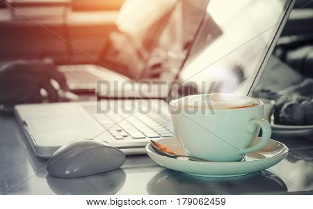 Activity image of vintage tone style cup of capuccino with people using laptop