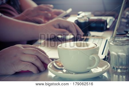 Cup of capuccino on the table with two man using laptop and smartphone in vintage color workplace