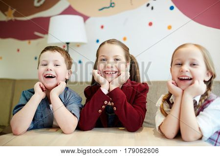 Ecstatic kids laughing at leisure in cafe