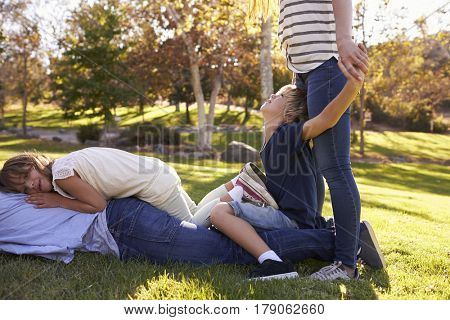Mother And Children Lying On Father In Park
