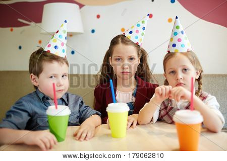 Dissatisfied kids with drinks looking at camera