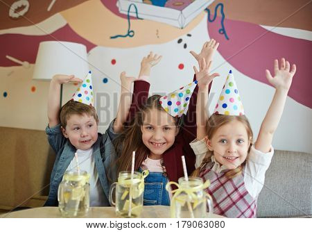 Ecstatic friends raising hands while enjoying party