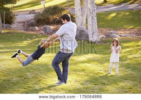 Father Swinging Son By His Arms In Park As Daughter Watches