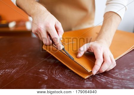 Handicraftsman cutting edges of new briefcase