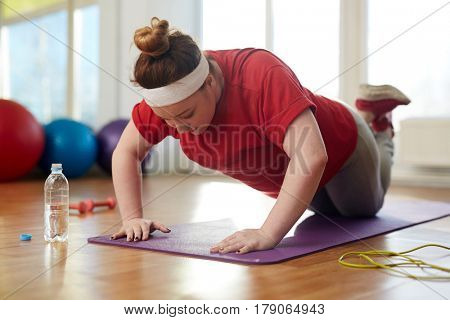 Portrait of young obese woman working out on yoga mat in sunlit fitness studio: performing knee push up exercise with effort to lose weight