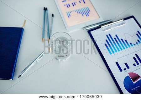 Close-up shot of working place: digital tablet, clipboard with documents, pencils, notebook and glass of water located on office desk