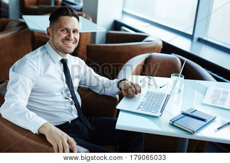 Stylish middle-aged businessman looking at camera with toothy smile while working on project in cozy small cafe, waist-up portrait
