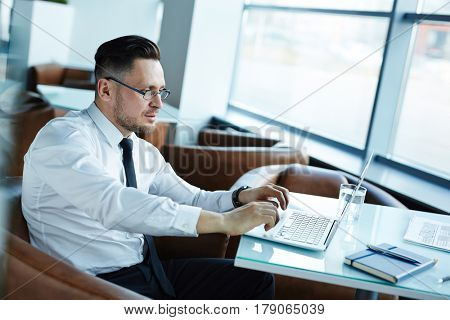 Waist-up portrait of confident middle-aged businessman working on presentation with help of modern laptop while sitting in office lobby, profile view