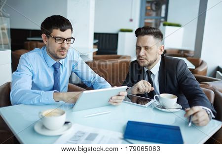 Two bearded businessmen in suits gathered together in cozy coffeehouse and analyzing results of accomplished project, waist-up portrait