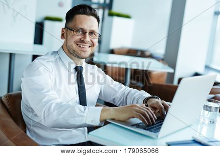 Waist-up portrait of cheerful middle-aged financial manager making corrections in annual accounting reports while sitting in spacious office lobby