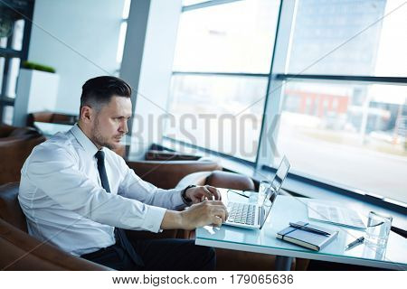 Profile view of handsome manager with stylish haircut sitting opposite panoramic cafe window and working on modern laptop, waist-up portrait