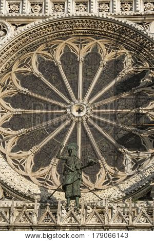 Monza (Brianza Lombardy Italy): historic cathedral exterior detail of the facade (Duomo): rose window and a bronze statue