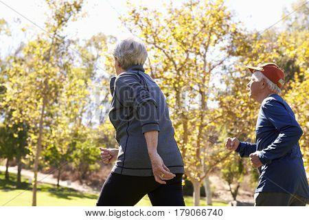 Rear View Of Senior Couple Power Walking Through Park