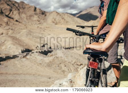 Close up image man hand on bicycle saddle. Two maountain bikers in Himalaya