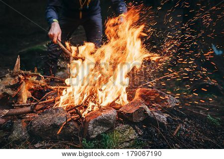 Man makes bonfire in the dark forest .