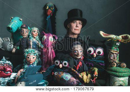 Puppeteer woman standing between her handmade puppets.