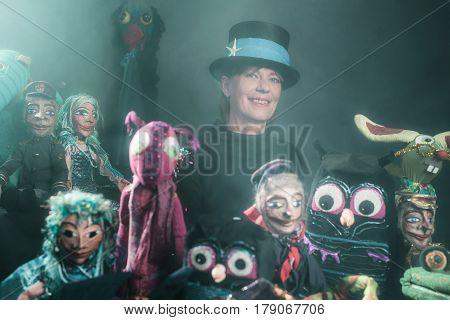 Mystical puppeteer standing between her handmade puppets.