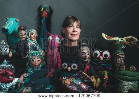 Studio Portrait Of Puppeteer Standing Between Handmade Puppets.